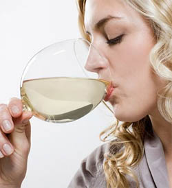 a photo of a woman drinking white wine from a glass