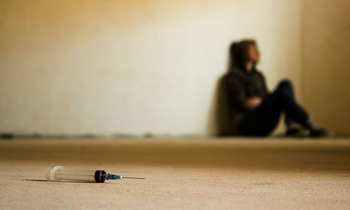 a photo of a person sitting on the floor next to a syringe