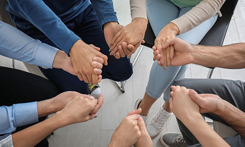 image of people holding hands during a group therapy session