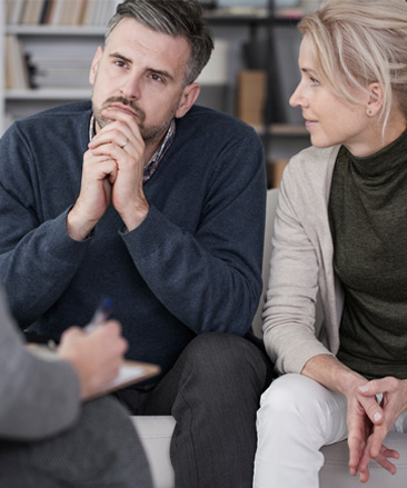 A man and woman talking to a counsellor