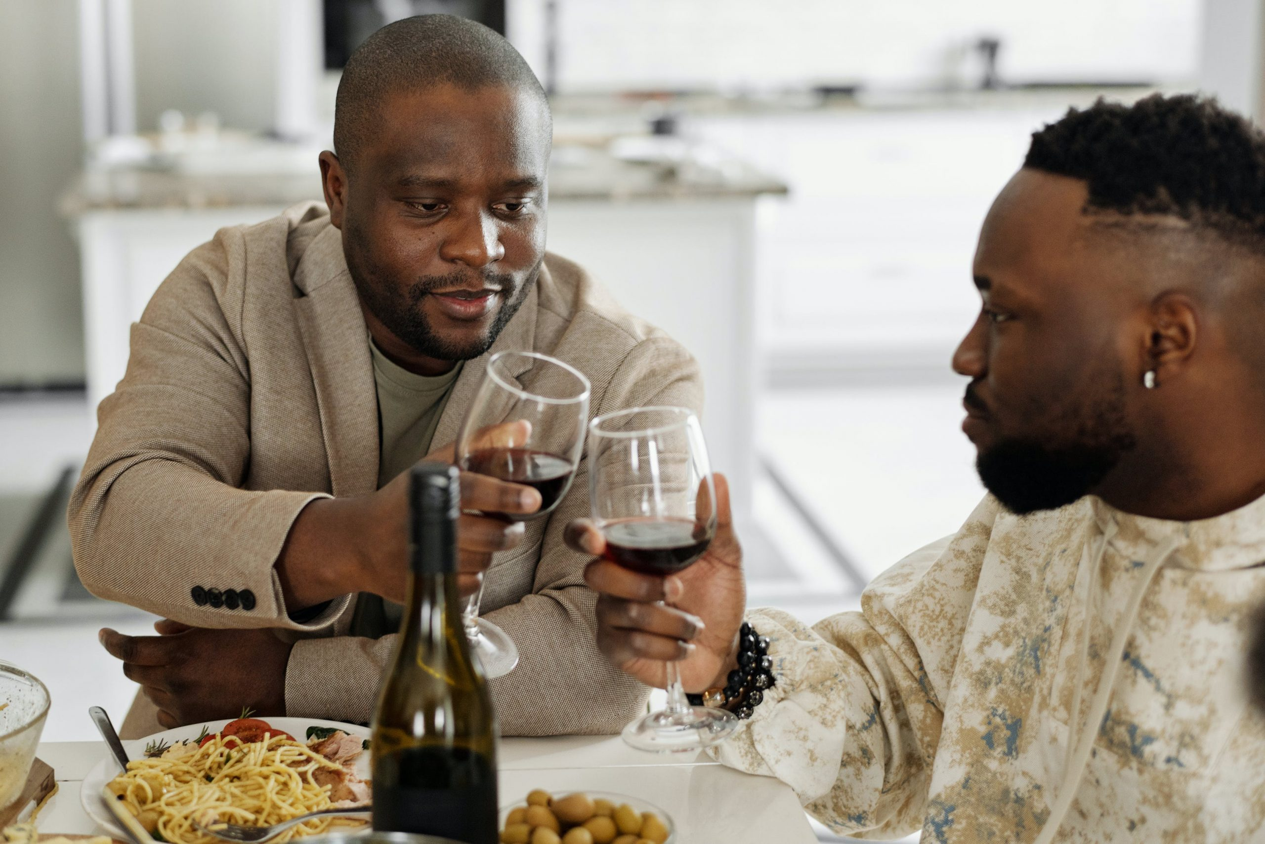 two men drinking wine at dinner