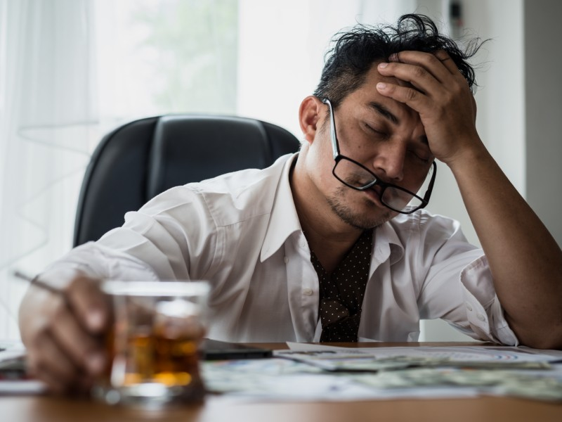 man stressed at work drinking