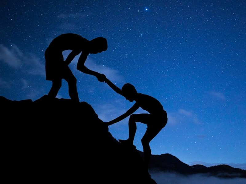an image showing a boy helping another climb higher