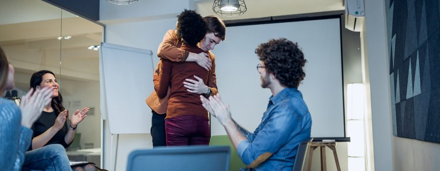 Two people embracing in group therapy