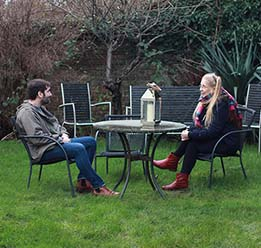Photo of two people sitting on a table in the garden